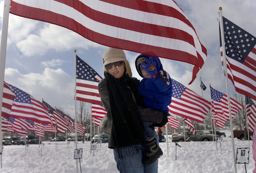 Kim Raff  |  The Salt Lake Tribune Heather holds her son Ricardo Ortega in the Field of Honor, flags to honor the 40 soldiers who have died in the War on Terror, at Taylorsville City Hall after Veterans Day Parade on Sunday.