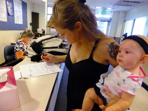 In this July 16, 2012, photo, Laura Fritz, 27, left, with her daughter Adalade Goudeseune fills out a form at the Jefferson Action Center, an assistance center in the Denver suburb of Lakewood. Both Fritz grew up in the Denver suburbs a solidly middle class family, but she and her boyfriend, who has struggled to find work, and are now relying on government assistance to cover food and $650 rent for their family. The ranks of America's poor are on track to climb to levels unseen in nearly half a century, erasing gains from the war on poverty in the 1960s amid a weak economy and fraying government safety net. (AP Photo/Kristen Wyatt)