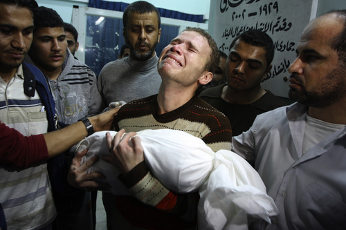 Jihad Masharawi weeps while he holds the body of his 11-month old son Ahmad, at Shifa hospital following an Israeli air strike on their family house, in Gaza City, Wednesday, Nov. 14, 2012. The Israeli military said its assassination of the Hamas military commander Ahmed Jabari, marks the beginning of an operation against Gaza militants. (AP Photo/Majed Hamdan)