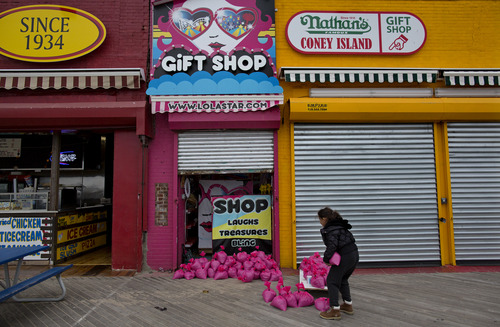 FILE - In this Oct. 28, 2012, file photo, Jessie Rivera, 10, of New York, brings pink sandbags to the door of the shop in New York. Americans cut back sharply on spending at retail businesses in October, an indication that some may still be cautious about the economy. Superstorm Sandy may have slowed business at the end of the month. The Commerce Department said Wednesday, Nov. 14, 2012, that sales dropped 0.3 percent after three months of gains. Auto sales fell 1.5 percent, the most in more than a year. (AP Photo/Craig Ruttle, File)