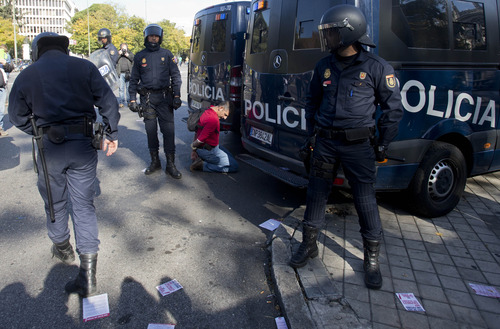 A man kneels down handcuffed next to police vans after being detained by the police during a general strike in Madrid, Wednesday Nov. 14, 2012. A Spanish Interior Ministry official says 32 people have been arrested and 15 people treated for minor injuries in disturbances as a general strike in Spain against austerity measures and economic reforms began. The General Workers Union said the nationwide stoppage, the second this year, was being heeded by nearly 100 percent of workers Wednesday in the automobile, energy, shipbuilding and constructions industries. (AP Photo/Paul White)