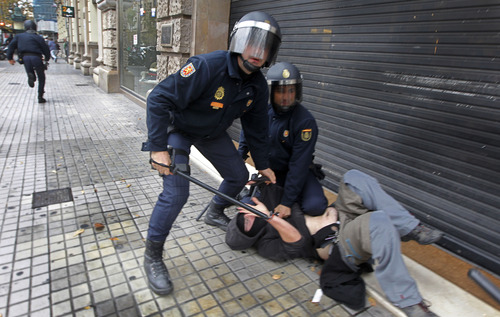 Riot police officers pin down a demonstrator during clashes with protestors in a general strike in Valencia, Spain, Wednesday, Nov. 14, 2012. Spain's main trade unions stage a general strike, coinciding with similar work stoppages in Portugal and Greece, to protest government-imposed austerity measures and labor reforms. The strike is the second in Spain this year. (AP Photo/ Fernando Hernandez)