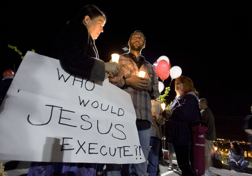 "Jim Urquhart  |  The Salt Lake Tribune Kristin Powers, left, of Salt Lake City hold a sign that reads ""Who would Jesus execute?!"" as she talks with Randy Gardner Jr., Ronnie Lee Gardner's nephew during a candle light vigil at a gathering of Ronnie Lee Gardner supporters Thursday, June 17, 2010 across from the Utah State Prison in Draper. Ronnie Lee Gardner was executed by firing squad. 6/17/10"