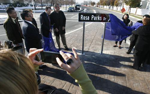 Scott Sommerdorf  |  The Salt Lake Tribune               Melissa Flores, foreground, snaps a photo Thursday as diginitaries, including West Valley City Councilman Corey Rushton and Jeanetta Williams, president of the NAACP Salt Lake Branch, pull away a covering to unveil the new Rosa Parks Drive sign at the southeast corner of the roundabout near the Utah Cultural Celebration Center in West Valley City.