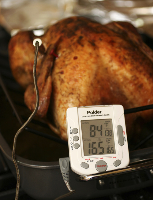 FILE- This Oct. 18, 2007 file photo shows a turkey with a thermometer. Federal guidelines state that your turkey is safe to eat when the innermost part of the thigh reaches 165 F. Some people say thigh meat tastes better at 170 F. If the turkey is stuffed, the stuffing must also reach 165 F.  (AP Photo/Larry Crowe, File)