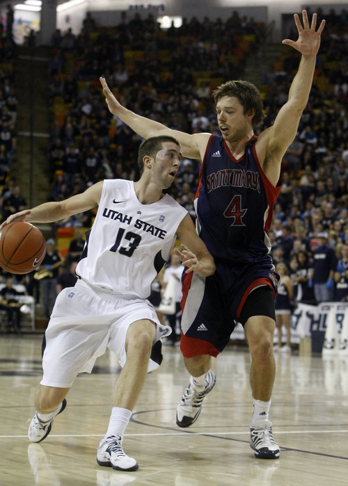 Chris Detrick  |  The Salt Lake Tribune Utah State Aggies guard Preston Medlin (13) is guarded by St. Mary's Gaels guard Matthew Dellavedova (4) during the second half of the game at Dee Glen Smith Spectrum Thursday November 15, 2012. St. Mary's won the game 67-58.