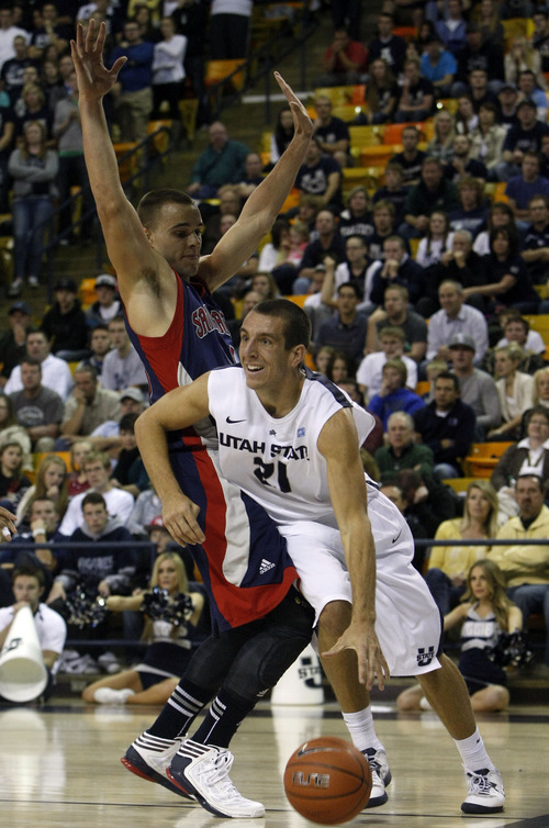 Chris Detrick  |  The Salt Lake Tribune Utah State Aggies guard/forward Spencer Butterfield (21) runs around St. Mary's Gaels forward Beau Levesque (15) during the second half of the game at Dee Glen Smith Spectrum Thursday November 15, 2012. St. Mary's won the game 67-58.