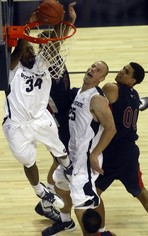 Chris Detrick  |  The Salt Lake Tribune Utah State Aggies forward Kyisean Reed (34) dunks the ball past St. Mary's Gaels forward Mitchell Young (3) and St. Mary's Gaels forward Brad Waldow (0) during the first half of the game at Dee Glen Smith Spectrum Thursday November 15, 2012. St. Mary's is winning the game 34-31.