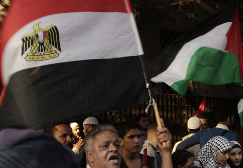 """Protesters wave the Egyptian and Palestinian flags during a protest in solidarity with Gaza after Israel launched its operation on Wednesday with the assassination of Hamas' top military commander in front of the Arab League building Cairo, Egypt, Thursday, Nov. 15, 2012. Egypt asked the United States to push Israel to stop its offensive against Hamas militants in the Gaza Strip, warning that the violence could """"escalate out of control,"""" the Foreign Ministry said Thursday. (AP Photo/Nariman El-Mofty)"""