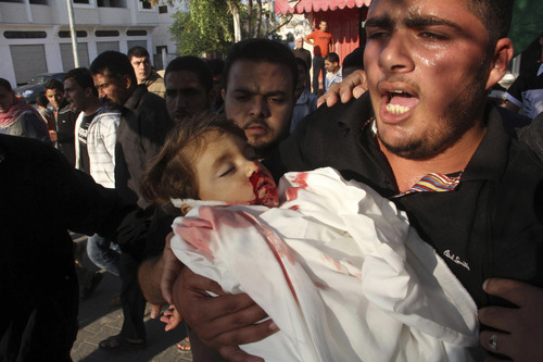 A relative carries the body of 2-year-old Palestinian Waleed Al-Abadlah during his funeral in the southern Gaza Strip city of Khan Younis on Thursday, Nov. 15, 2012. According to the family, Al-Abadlah died from wounds sustained in an Israeli air strike near his home. Palestinian militants hit Israel with nearly 150 rockets on Thursday, as Israel continued a campaign of airstrikes on militant targets across the Gaza Strip. (AP Photo/Hatem Omar)