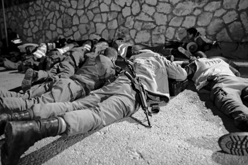Israeli soldiers take cover as an air raid siren warns of incoming rockets before the funeral of Aaron Smadja, one of the three Israelis killed by a rocket fired from Gaza, at a cemetery in the southern town of Kiryat Malachi, Thursday, Nov. 15, 2012. (AP Photo / Tsafrir Abayov)