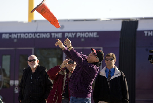 "Kim Raff  |  The Salt Lake Tribune Bill Coker, of Red Iguana, joins business owners on North Temple Thursday to celebrate completion of the major construction of the new TRAX line to the airport with a ""cone toss"" near the 1940 West North Temple station in Salt Lake City."