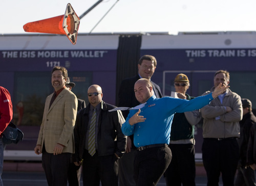 "Kim Raff  |  The Salt Lake Tribune Zach Fullmer, a personal banker with Wells Fargo, joins business owners on North Temple Thursday to celebrate completion of the major construction of the new TRAX line to the airport with a ""cone toss"" near the 1940 West North Temple station in Salt Lake City. Fullmer tossed the cone 50 yards."