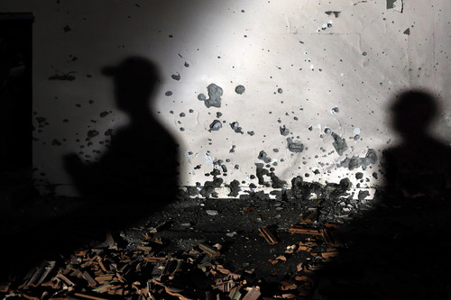 Israeli soldiers examine a damaged wall of a house hit by a rocked fired from the Gaza Strip at Be'er Tuvia Regional Council, Friday, Nov. 16, 2012. Fierce clashes between Israeli forces and Gaza militants are continuing for the third day. (AP Photo / Tsafrir Abayov)