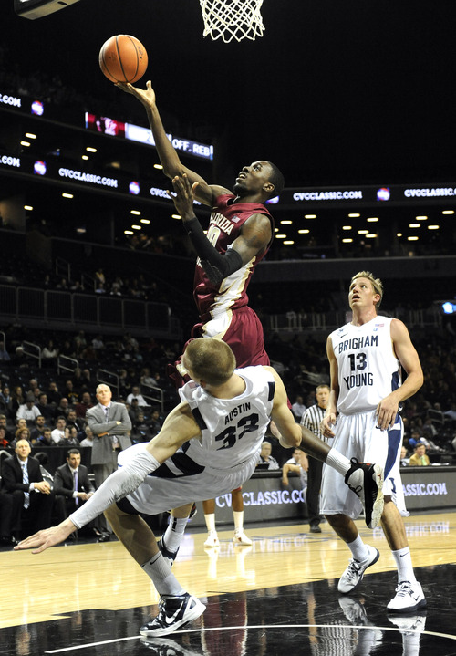 Florida State's Okaro White (10) drives to the basket over Brigham Young's Nate Austin (33) and Brock Zylstra (13) in the first half of the Coaches vs. Cancer Classic basketball game on Friday, Nov., 16, 2012, at Barclays Center in New York. Florida State won 88-70. (AP Photo/Kathy Kmonicek)