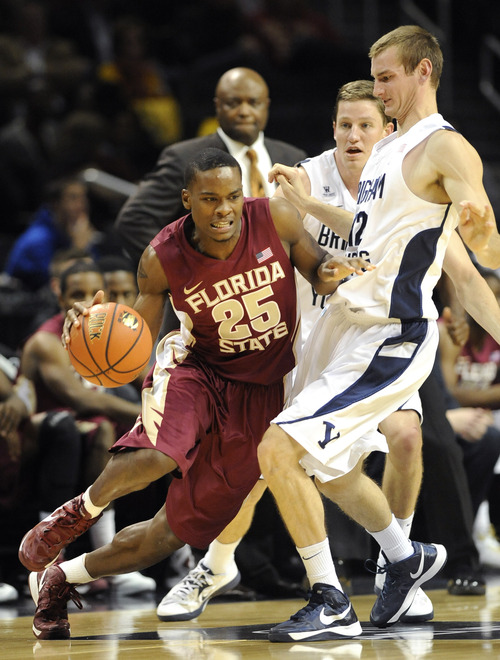 Florida State's Aaron Thomas (25) drives the ball around Brigham Young's Josh Sharp (12) in the first half of the Coaches vs. Cancer Classic basketball game on Friday, Nov., 16, 2012, at Barclays Center in New York. Florida State won 88-70. (AP Photo/Kathy Kmonicek)