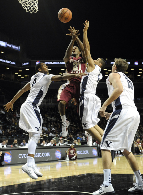 Florida State's Michael Snaer (21) is surrounded by Brigham Young's Brandon Davies (0), Raul Delgado (1) and Brock Zylstra (13) in the first half of the Coaches vs. Cancer Classic basketball game on Friday, Nov., 16, 2012, at Barclays Center in New York. (AP Photo/Kathy Kmonicek)