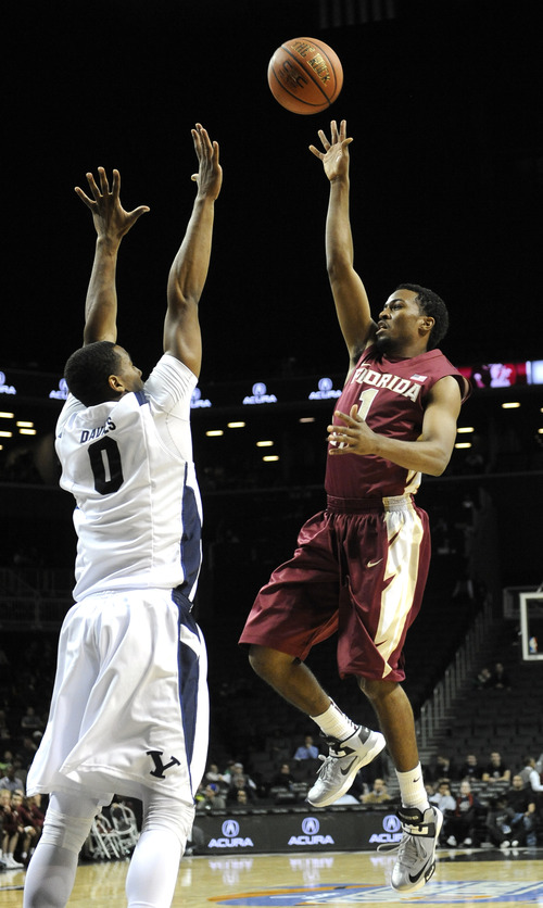 Florida State's Devon Bookert shoots (1) over Brigham Young's Brandon Davies (0) in the first half of the Coaches vs. Cancer Classic basketball game on Friday, Nov., 16, 2012, at Barclays Center in New York. (AP Photo/Kathy Kmonicek)