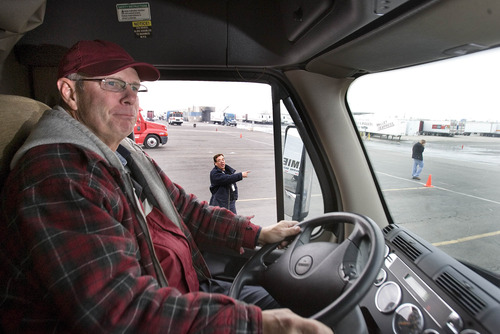 Paul Fraughton  |   Salt Lake Tribune Lance Williamson, of Eugene Oregon listens to his instructor Brian Lillie who shouts out directions as Williamson  backs his big rig  between orange cones, at  CR England's  truck driving range.  Friday, November 16, 2012