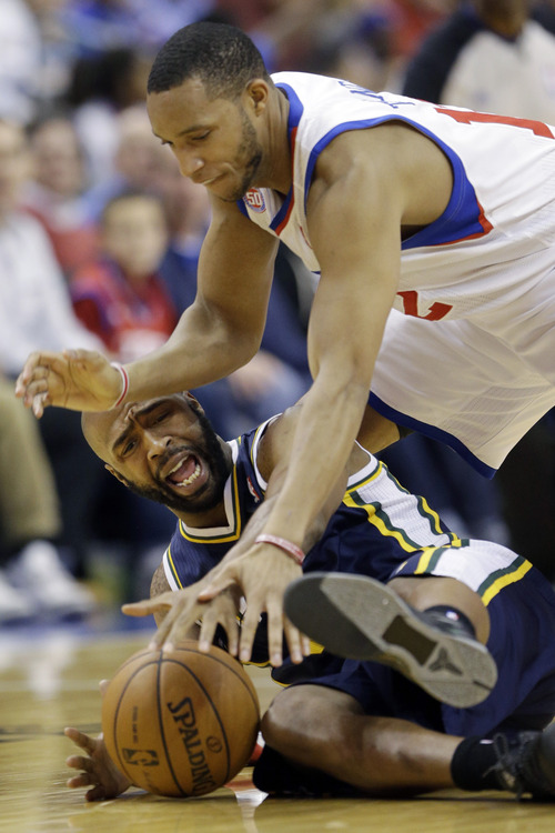 Philadelphia 76ers' Evan Turner, top, struggles for a loose ball with Utah Jazz's Jamaal Tinsley in the second half of an NBA basketball game, Friday, Nov. 16, 2012, in Philadelphia. Philadelphia won 99-93. (AP Photo/Matt Slocum)