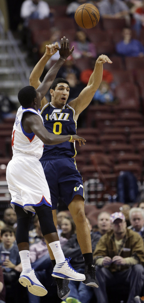 Utah Jazz's Enes Kanter, right, of Turkey, passes the ball away from Philadelphia 76ers' Jrue Holiday in the first half of an NBA basketball game on Friday, Nov. 16, 2012, in Philadelphia. (AP Photo/Matt Slocum)