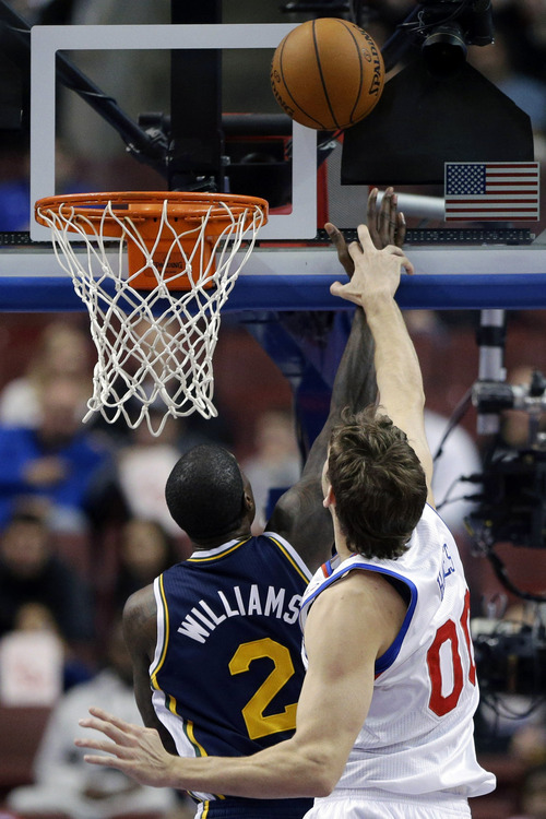 Philadelphia 76ers' Spencer Hawes (00) tries to block a shot by Utah Jazz's Marvin Williams in the first half of an NBA basketball game on Friday, Nov. 16, 2012, in Philadelphia. (AP Photo/Matt Slocum)