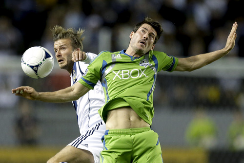 Los Angeles Galaxy's David Beckham, left, battles Seattle Sounders' Brad Evans for the ball during the first half of an MLS Western Conference finals soccer game, Sunday, Nov. 11, 2012, in Carson, Calif. (AP Photo/Chris Carlson)