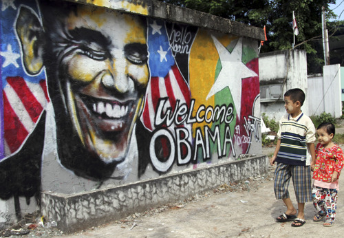 Myanmar children walk near a graffiti painted by Myanmar artist Arker Kyaw to welcome U.S. President Barack Obama on a street in Yangon, Myanmar, Saturday, Nov. 17, 2012. Word of Obama's historic visit has spread quickly around Yangon, which is readying itself with legions of hunched workers painting fences and curbs, pulling weeds and scraping grime off old buildings in anticipation of the president's Monday arrival. (AP Photo/Khin Maung Win)
