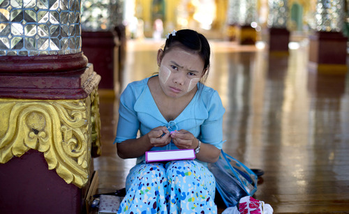 In this picture taken on Thursday, Nov. 15, 2012, a Buddhist devotee takes a break from prayers at Shwedagon Pagoda in Yangon, Myanmar. Word of U.S. President Barack Obama's historic visit has spread quickly around Yangon, which is readying itself with legions of hunched workers painting fences and curbs, pulling weeds and scraping grime off old buildings in anticipation of the president's Monday arrival. (AP Photo/Gemunu Amarasinghe)