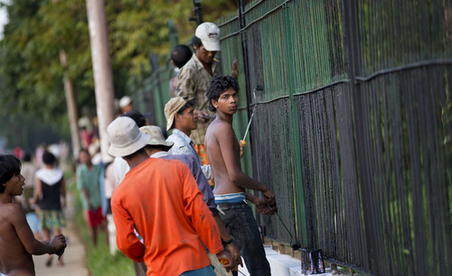 Workers paint the fence of Yangon University, in which American president Barack Obama is scheduled to deliver a speech in Yangon, Myanmar, Saturday, Nov. 17, 2012. Word of Obama's historic visit has spread quickly around Yangon, which is readying itself with legions of hunched workers painting fences and curbs, pulling weeds and scraping grime off old buildings in anticipation of the president's Monday arrival.(AP Photo/Gemunu Amarasinghe)