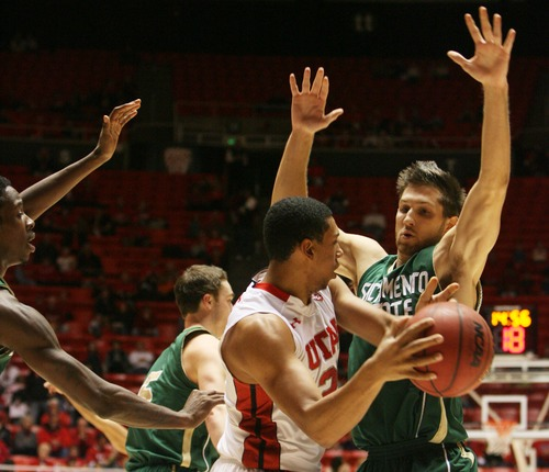 Kim Raff  |  The Salt Lake Tribune University of Utah player Jordan Loveridge looks to pass past Sacramento State player Joe Eberhard during a men's basketball game at the Huntsman Center in Salt Lake City on November 16, 2012.