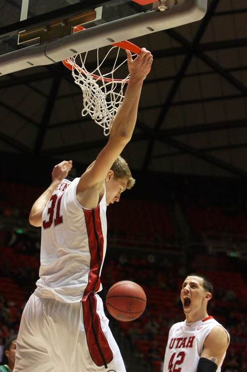 Kim Raff  |  The Salt Lake Tribune University of Utah player (right) Jason Washburn reacts as teammate Dallin Bachynski dunks the ball against Sacramento State during a men's basketball game at the Huntsman Center in Salt Lake City on November 16, 2012. They went on to lose the game 71-74.