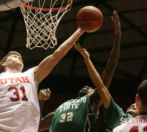 Kim Raff  |  The Salt Lake Tribune (left) University of Utah player Dallin Bachynski rebounds the ball over the hands of Sacramento State player John Dickson during a men's basketball game at the Huntsman Center in Salt Lake City on November 16, 2012. They went on to lose the game 71-74.