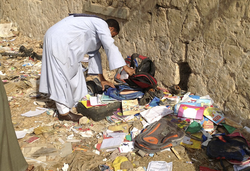 RETRANSMISSION FOR ALTERNATE CROP -- An Egyptian looks through books and school bags that were strewn along the tracks at the scene where a speeding train crashed into a bus carrying children to their kindergarten, killing at least 47, officials said, near Assiut  in southern Egypt, Saturday, Nov. 17, 2012. The bus was carrying more than 50 children between 4 and 6 years old when it was hit by a train near al-Mandara village in Manfaloot district in the province of Assiut, a security official said, adding that it appears that the railroad crossing was not closed as the train sped toward it. (AP Photo/Mamdouh Thabet)