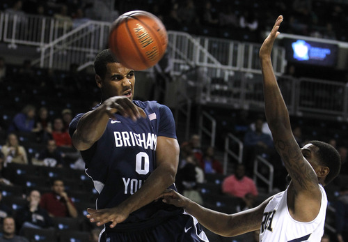 BYU's Brandon Davies, left, passes away from Notre Dame's Eric Atkins during the second half of their NCAA college basketball game in the consolation round of the Coaches vs. Cancer Classic at the Barclays Center, Saturday, Nov. 17, 2012, in New York.  Notre Dame defeated BYU, 78-68. (AP Photo/Jason DeCrow)