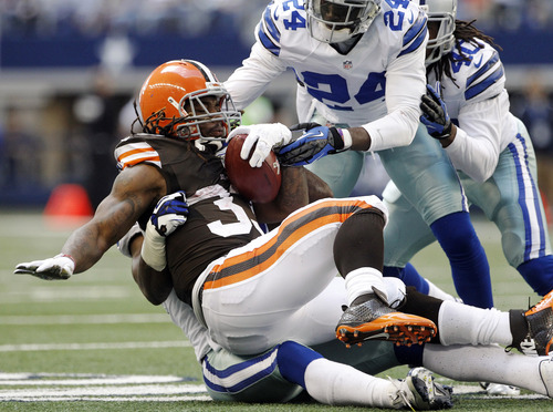 Dallas Cowboys' Bruce Carter, rear, Morris Claiborne (24) and Danny McCray (40) combine to stop a run by Cleveland Browns' Trent Richardson (33) in the second half of an NFL football game, Sunday, Nov. 18, 2012, in Arlington, Texas. (AP Photo/Brandon Wade)