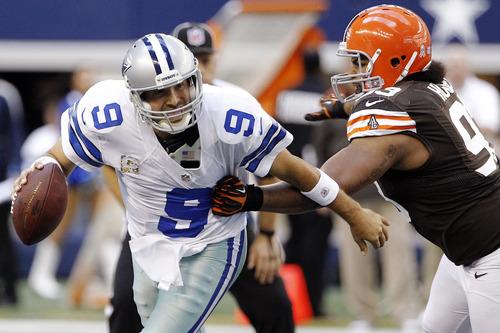 Dallas Cowboys quarterback Tony Romo (9) escapes a tackle attempt by Cleveland Browns' John Hughes (93) in the second half of an NFL football game, Sunday, Nov. 18, 2012, in Arlington, Texas. (AP Photo/Brandon Wade)