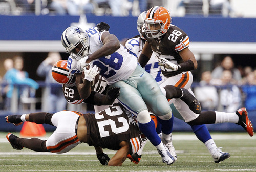 Cleveland Browns' Buster Skrine (22), D'Qwell Jackson (52) and Trevin Wade (26) combine to stop a run by Dallas Cowboys' Felix Jones in the second half of an NFL football game, Sunday, Nov. 18, 2012, in Arlington, Texas. (AP Photo/Brandon Wade)