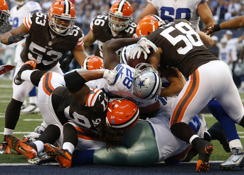 Dallas Cowboys running back Felix Jones (28) breaks into the end zone for a touchdown through Cleveland Browns defenders Jabaal Sheard (97) and L.J. Fort (58) as Craig Robertson (53) and Emmanuel Acho (59) watch in the second half of an NFL football game, Sunday, Nov. 18, 2012, in Arlington, Texas. (AP Photo/Sharon Ellman)