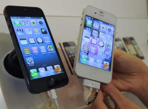 The new iPhone 5, left,  and the iPhone 4S are shown at the AT&T Mobility store, Friday, Sept. 21, 2012, in Fredericksburg, Va. (AP Photo/The Free Lance-Star, Robert A. Martin)