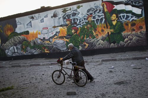 A Palestinian man walks past a graffiti depicting Palestinian soldiers, right, figthing against Israeli soldiers moments after an Israeli forces strike in Gaza City, Sunday, Nov. 18, 2012. The Israeli military widened its range of targets in the Gaza Strip on Sunday to include the media operations of the Palestinian territory's Hamas rulers, sending its aircraft to attack two buildings used by both Hamas and foreign media outlets. (AP Photo/Bernat Armangue)