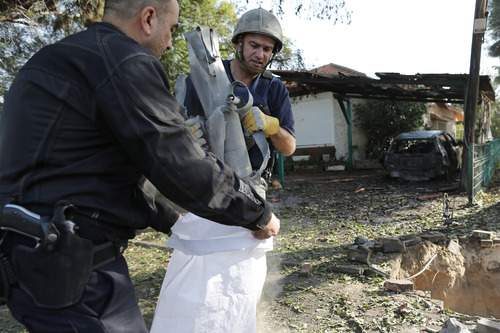 Israeli police sappers remove the remains of a rocket fired by Palestinian militants from Gaza Strip, that hit a house in Ashkelon, southern Israel, Sunday, Nov. 18, 2012. Israel launched the operation last Wednesday by assassinating Hamas' military chief and carrying out dozens of airstrikes on rocket launchers and weapons storage sites. Over the weekend, the operation began to target Hamas government installations as well, including the offices of its prime minister. (AP Photo/Tsafrir Abayov)