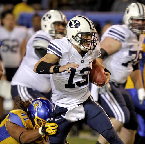 Brigham Young quarterback Riley Nelson (13) breaks a tackle by San Jose State defensive end David Tuitupou (41) in the first quarter of an NCAA college football game in San Jose, Calif., Saturday, Nov. 17, 2012. (AP Photo/John Storey)