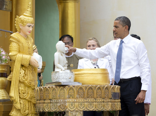 "U.S. President Barack Obama ""douses eleven flames"" as he tours the Shwedagon Pagoda with Secretary of State Hillary Rodham Clinton in Yangon, Myanmar, Monday, Nov. 19, 2012. This is the first visit to Myanmar by a sitting U.S. president. (AP Photo/Carolyn Kaster)"