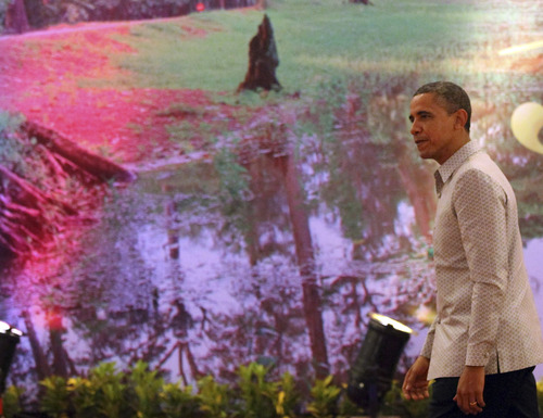 U.S. President Barack Obama walks to the reception room past a wall decoration prior to the gala dinner in Phnom Penh, Cambodia, Monday, Nov. 19, 2012. Obama is in Cambodia on the final leg of his three-country tour of Southeast Asia. (AP Photo/Apichart Weerawong)