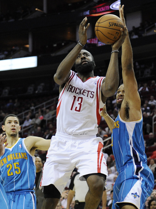 Houston Rockets' James Harden (13) goes to the basket between New Orleans Hornets defenders Austin Rivers (25) and Xavier Henry in the second half of an NBA basketball game Wednesday, Nov. 14, 2012, in Houston. The Rockets won 100-96. Harden scored 30 points. (AP Photo/Pat Sullivan)