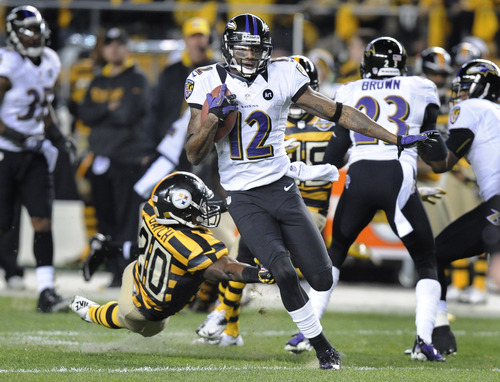 Baltimore Ravens' Jacoby Jones (12) returns a punt past Pittsburgh Steelers' Baron Batch (20)on his way to a touchdown in the first quarter of an NFL football game on Sunday, Nov. 18, 2012, in Pittsburgh. (AP Photo/Don Wright)