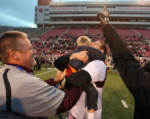 Steve Griffin | The Salt Lake Tribune   Jordan head coach Eric Kjar hugs his four-year-old son Carter at the end of the State 5A football championship game against  Syracuse at Rice Eccles Stadium in Salt Lake City, Utah Friday November 16, 2012.  Jordan beat Syracuse for the title.
