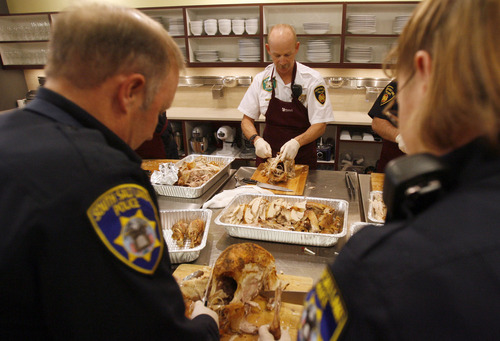Francisco Kjolseth  |  The Salt Lake Tribune South Salt Lake officers Paul McCullough, left, and Jennifer Smartt, right, join South Salt Lake Battalion Chief Kent Robertson in carving up turkeys. The South Salt Lake Police Athletics/Activities League (PAL) youth participants prepared Thanksgiving dinner for their families and people in need within their communities. For their fifth year of the event, Norbest donated 24 turkeys that the kids cooked up alongside the South Salt Lake Police and Fire departments at the Viking Cooking School at Kimball Distributing on Tuesday, November 20, 2012. South Salt Lake PAL programs provide educational, athletic and recreational activities aimed at building self-esteem and trust between police and youth.