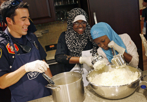Francisco Kjolseth  |  The Salt Lake Tribune Ahado Mberwa, 13, right, puts some muscle into it as she and Asma Dahir, 13, make mashed potatoes with South Salt Lake firefighter Justin Leavitt. The South Salt Lake Police Athletics/Activities League (PAL) youth participants prepared Thanksgiving dinner for their families and people in need within their communities. For their fifth year of the event, Norbest donated 24 turkeys that the kids cooked up alongside the South Salt Lake Police and Fire departments at the Viking Cooking School at Kimball Distributing on Tuesday, November 20, 2012. South Salt Lake PAL programs provide educational, athletic and recreational activities aimed at building self-esteem and trust between police and youth.